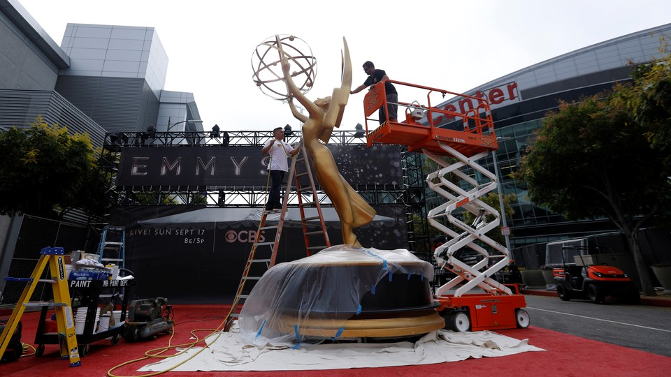 Workers install a large Emmy statue ahead of the 2017 awards ceremony