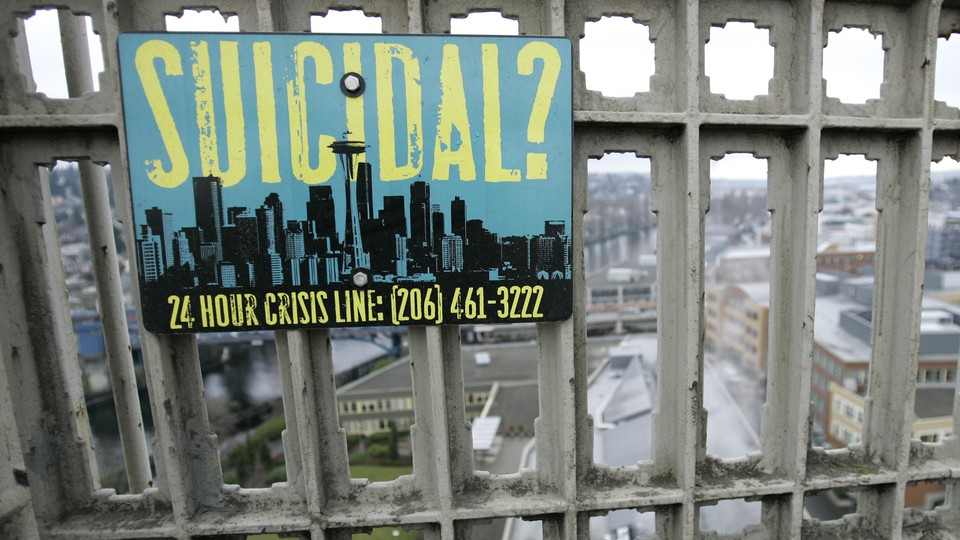 A sign advising of the phone number for a suicide-prevention hotline is shown on the Aurora Bridge in Seattle.