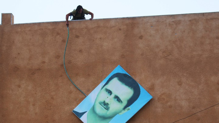 A rebel fighter stands atop a building and takes down a large picture of Assad after rebels captured the area in 2015.