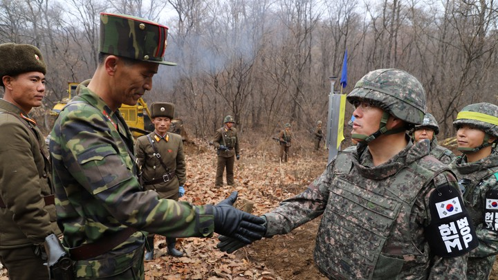 A South Korean military officer and a North Korean military officer shake hands near the demilitarized zone separating the two Koreas on November 22.