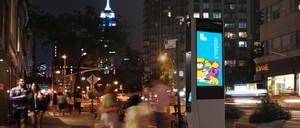 A LinkNYC kiosk glows on a Manhattan sidewalk.