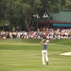 A golfer swings during a tournament as a crowd looks on.