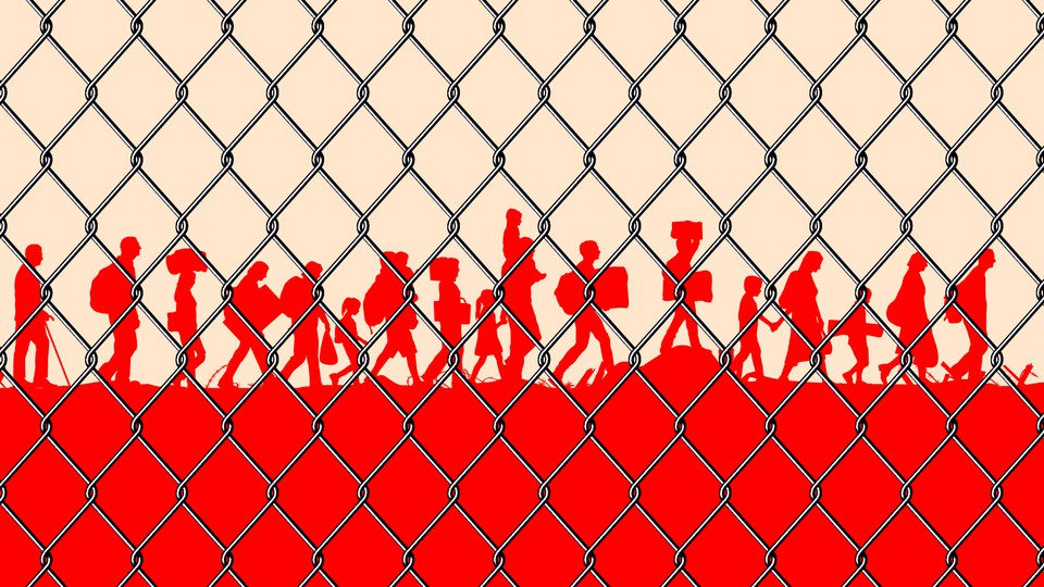 Silhouettes of migrants behind a chain-link fence.