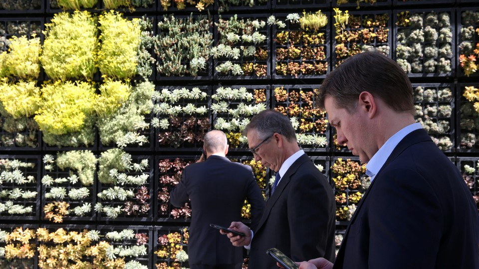 People look at their cellphones in front of a wall garden during the Milken Institute Global Conference in Beverly Hills, California, in May 2017.