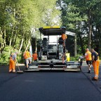 Workmen stand behind a construction vehicle smoothing asphalt on a road