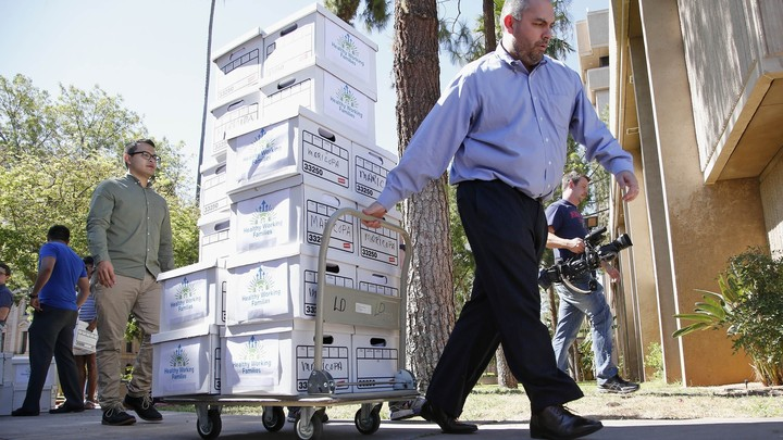 Arizona State Elections Director Eric Spencer hauls boxes of signatures from campaigners seeking to place a minimum-wage increase on the 2016 ballot.