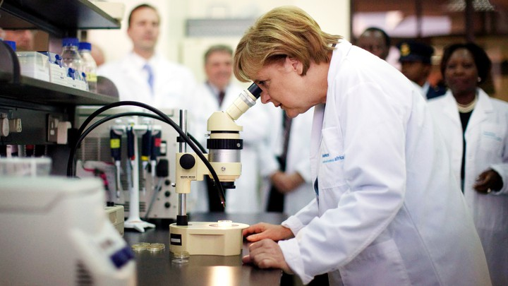 Angela Merkel looks through a microscope while wearing a white lab coat.