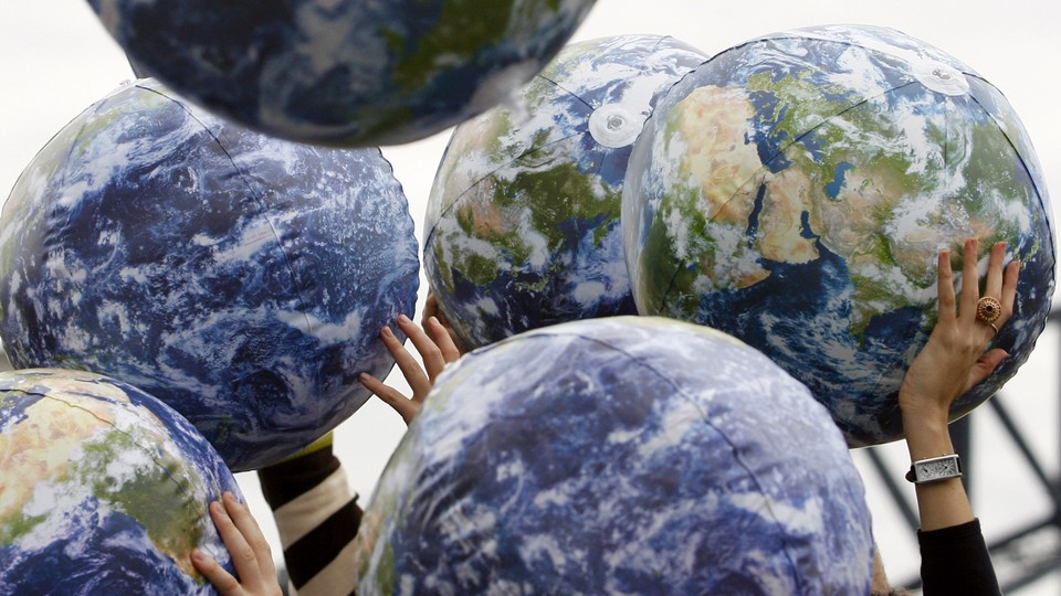 People hold up inflatable world globes during World Environment Day celebrations in central Sydney June 5, 2009.