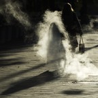A woman walks down a street with her shadow caught in steam rising from the ground