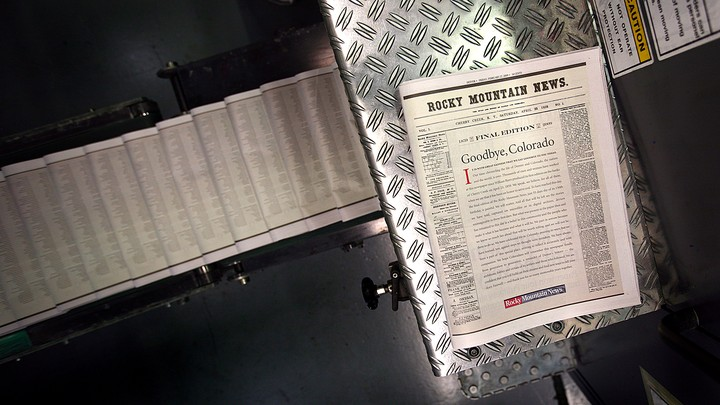 A final edition of the Rocky Mountain News sits atop a piece of the presses on February 26, 2009