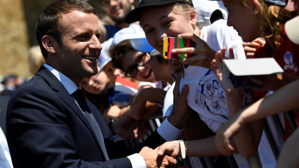 French President Emmanuel Macron shakes hands at a ceremony.
