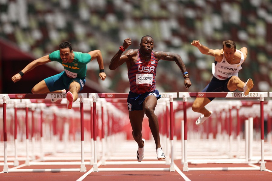 Several runners leap over and past the final hurdle in a race.