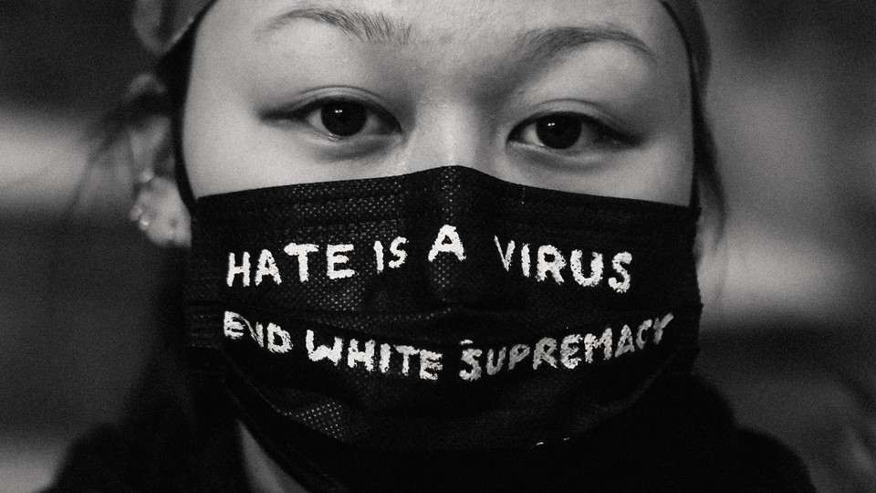 """woman wearing a mask that says """"Hate is a virus / End white supremacy"""""""
