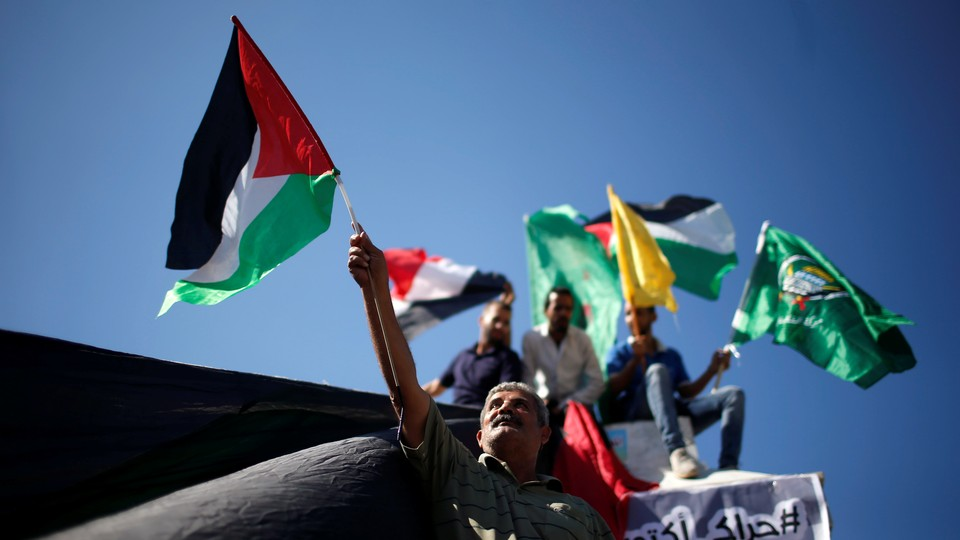 Palestinians celebrate after Hamas said it reached a deal with Palestinian rival Fatah, in Gaza City.