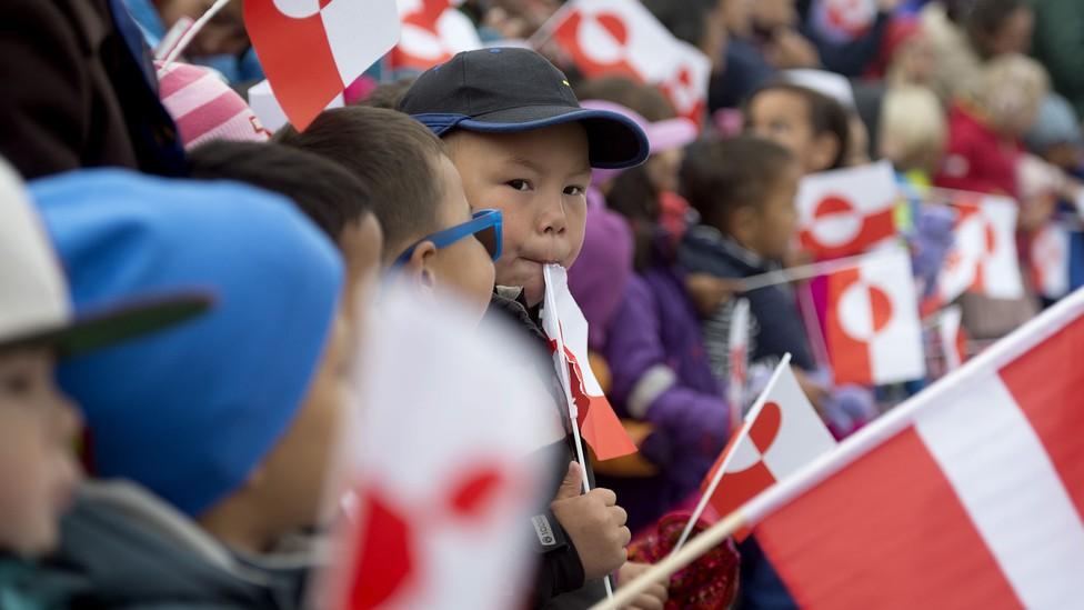 Children holding Greenland's national flag