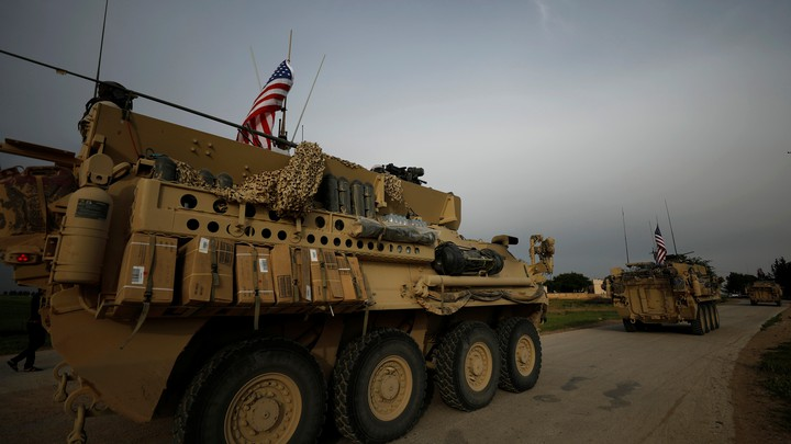 U.S. military vehicles drive in the town of Darbasiya next to the Turkish border, Syria, on April 28, 2017.