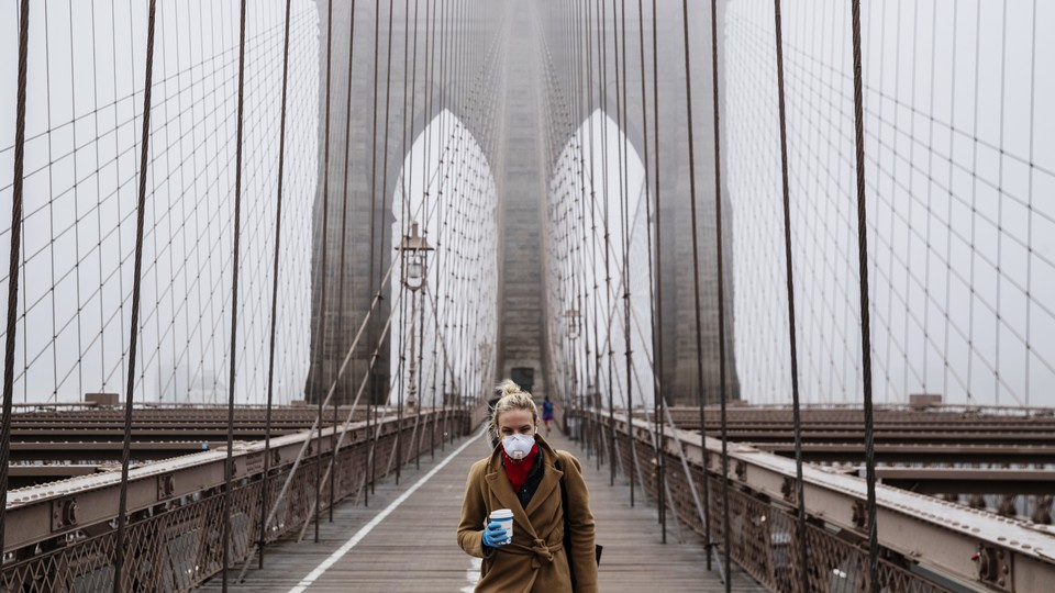 A woman wearing a mask and carrying a coffee cup on a bridge