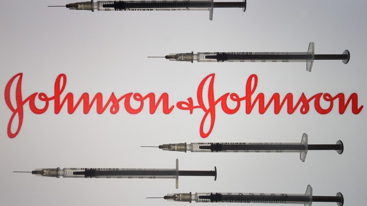 Vaccine needles surrounding the Johnson & Johnson logo
