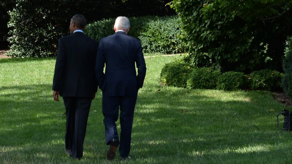 Former Presidents Barack Obama and Bill Clinton walk through a garden, facing away from the camera.