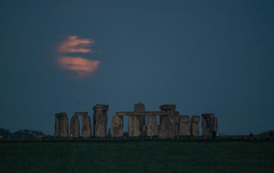 A hazy moon is seen beyond Stonehenge.