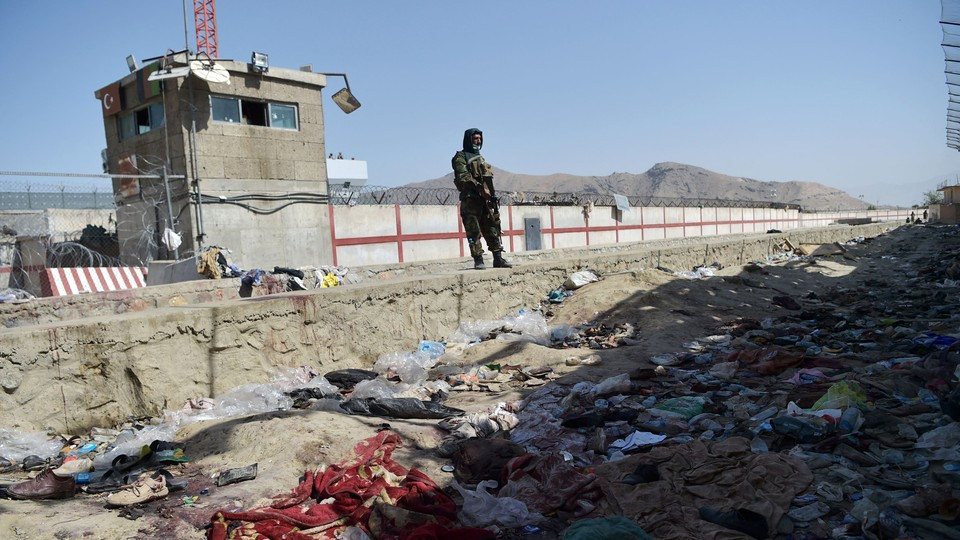A Taliban fighter stands guard at the site of the August 26 twin suicide bombs