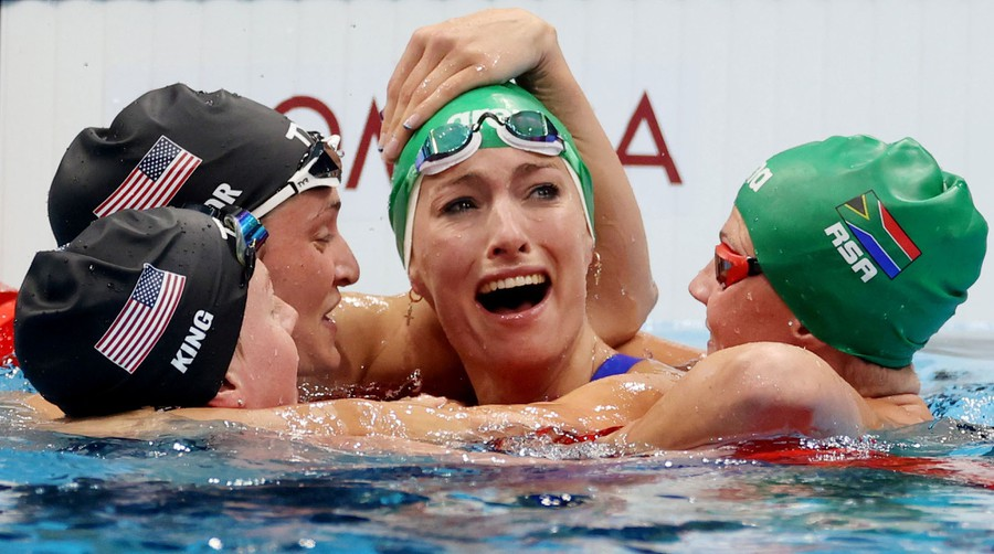 Four swimmers celebrate and hug in a pool after a race.