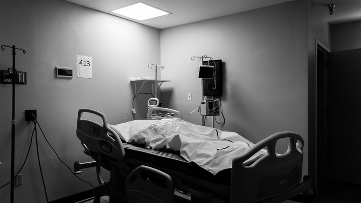 A hospital bed with a deceased patient in a body bag
