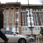 A young man walks past a corridor with new development in Washington, D.C.