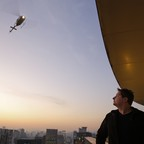 A man looks at an arriving helicopter.