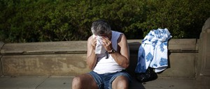 A man wipes his forehead in a park on a hot summer day.