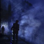 At night, a firefighter passes through smoke to survey a building destroyed by a wildfire near Calistoga, California.