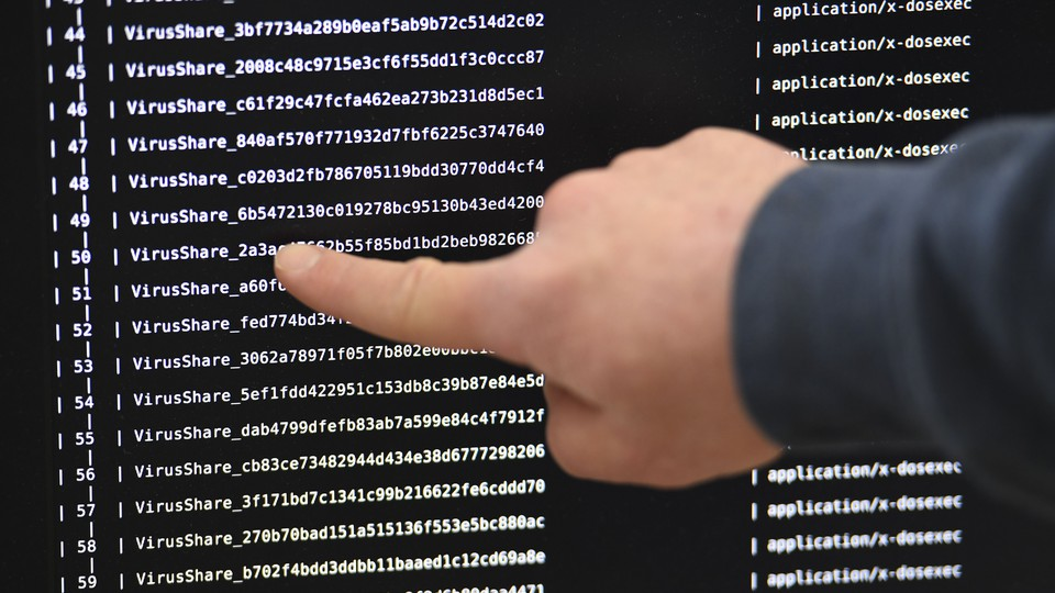 An IT researcher points at a computer infected by a ransomware.