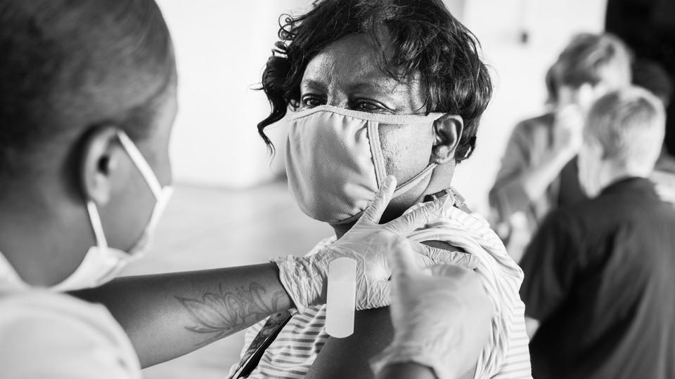 A man in a mask getting a vaccine