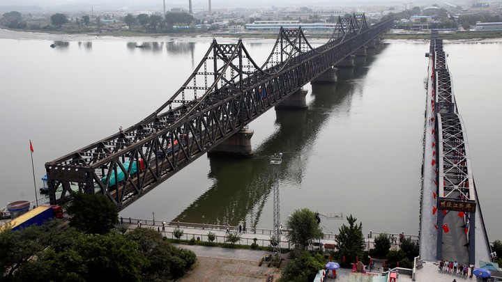 Vehicles cross a bridge connecting North Korea and China