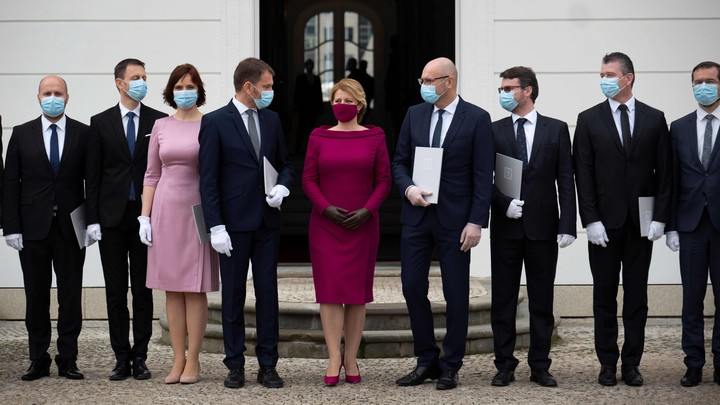 Slovakia's government stands in a row while wearing masks.