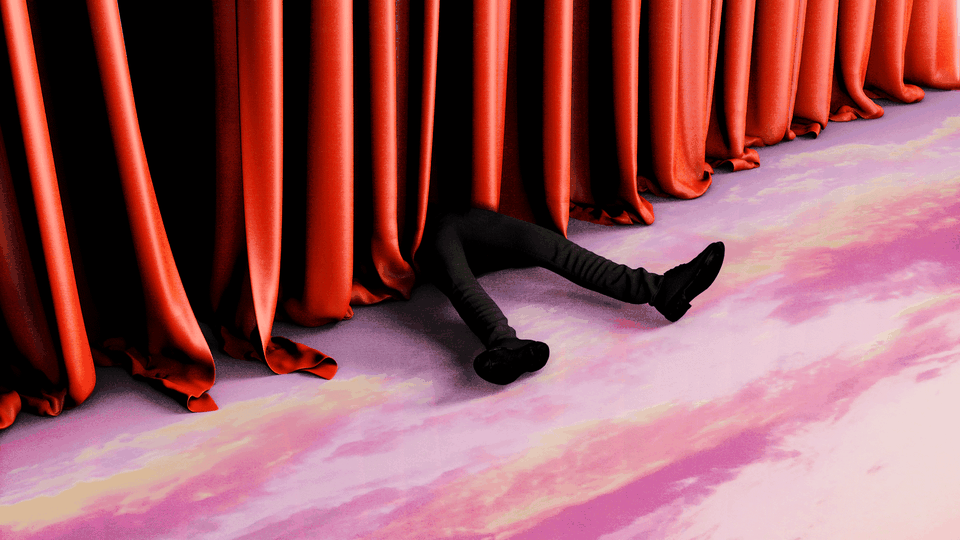 Legs are seen next to a red curtain