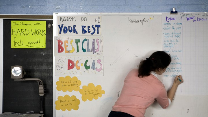 A woman writes on a dry-erase board at the front of a classroom. Her back faces the camera.