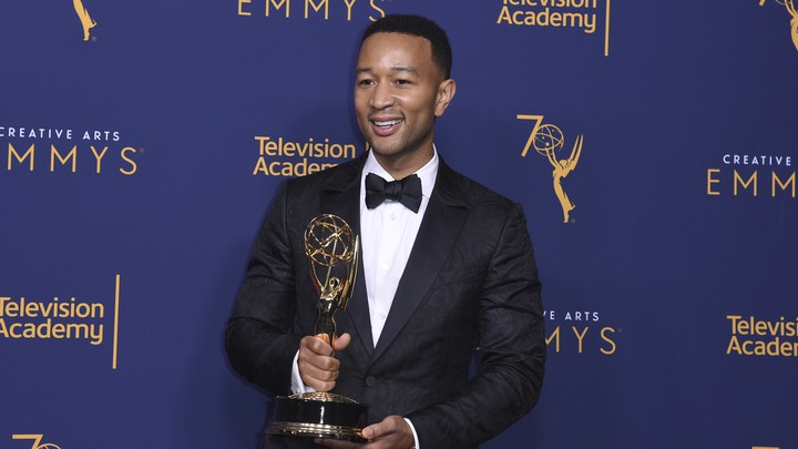 John Legend holding his Emmy award