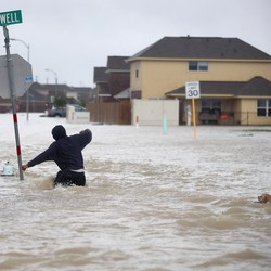 A person wades through high floodwaters.