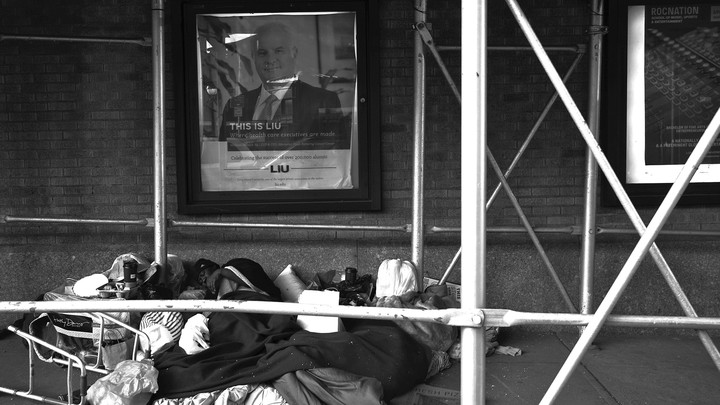 """A pile of belongings on a city street, below a poster saying """"This is where health executives are made"""""""