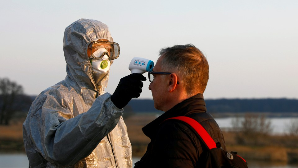 A security agent takes a man's temperature at the Polish-German border.