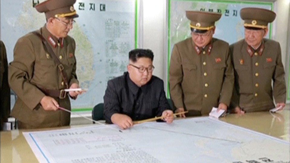 Kim Jong Un and his military advisers examine a large map