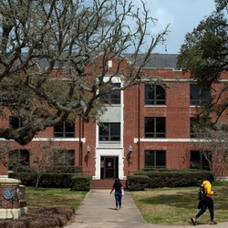 Two students walk near a building at Prairie View A&M University.