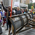 In downtown Pittsburgh, marchers pass a city plow truck parked in the middle of the road as they protest the shooting death of Antwon Rose Jr. on Tuesday, June 26, 2018. Rose was fatally shot by a police officer seconds after he fled a traffic stop June 19, in the suburb of East Pittsburgh.
