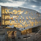 A light rail train pass through the new, Snøhetta-designed Calgary Central Library at dusk.