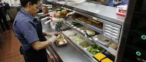 Two women prepare food at a McDonald's restaurant.
