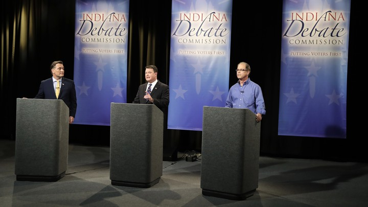 Three senatorial candidates stand at lecterns on a debate stage.
