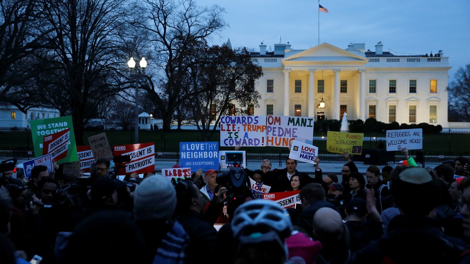 Demonstrators rally against the Trump administration's new travel ban outside of the White House.