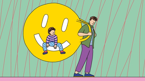 A father carries a giant backpack in the shape of a smiley face while his child sits on the backpack.