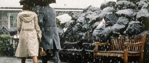 A photo of Londoners walking past piles of trash during a 1979 garbage strike.